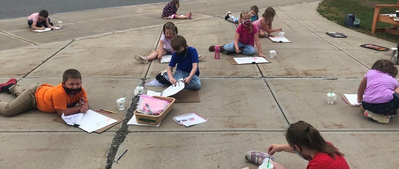 Children doing artwork on sidewalk