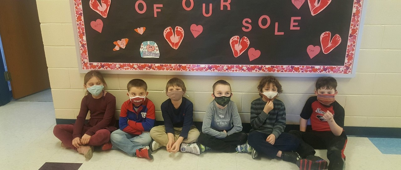 Students with Valentines Day Bulletin Board